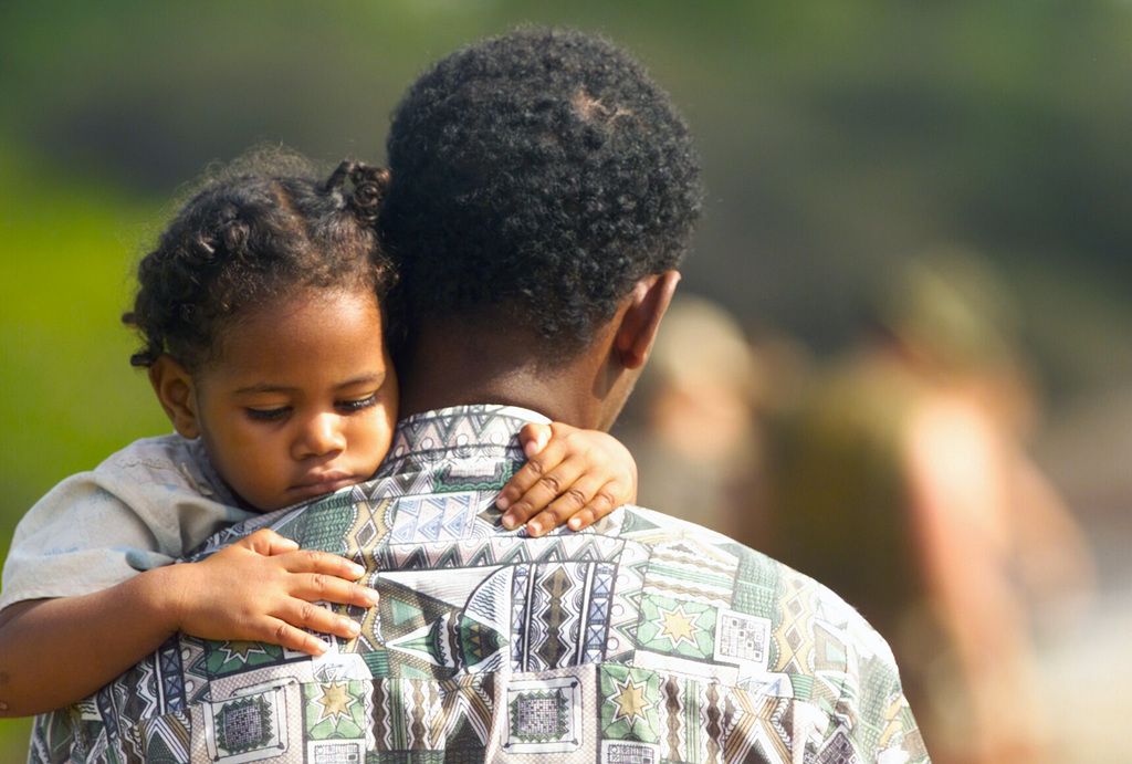 As Marines from the 13th Marine Expeditionary Unit (Special Operations Capable) (MEU (SOC)), Camp Pendleton, California, work on the bridge into Faza; Kenaya a Kenyan carries his daughter across safely in his arms. The bridge is being built as part of community relations during Exercise EDGE MALLET 02 in Faza, Kenya