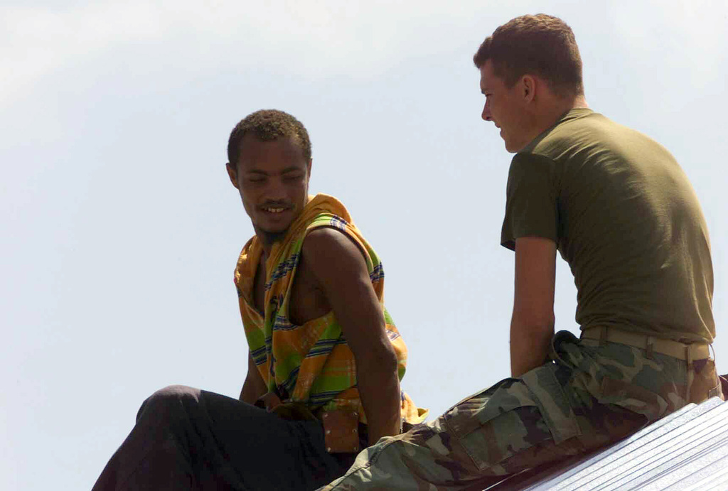 Lance Corporal Jason S. Leonard, USMC, Combat Engineer, 1ST CEB (Combat Engineer Battalion), BLT 1/4 (Battalion Landing Team), from the 13th Marine Expeditionary Unit (Special Operations Capable) (MEU (SOC)) takes a moment to talk with his Kenyan co-worker while working on the roof of the schoolhouse in Faza. The schoolhouse is being built as part of community relations during Exercise EDGE MALLET 02 in Kenya