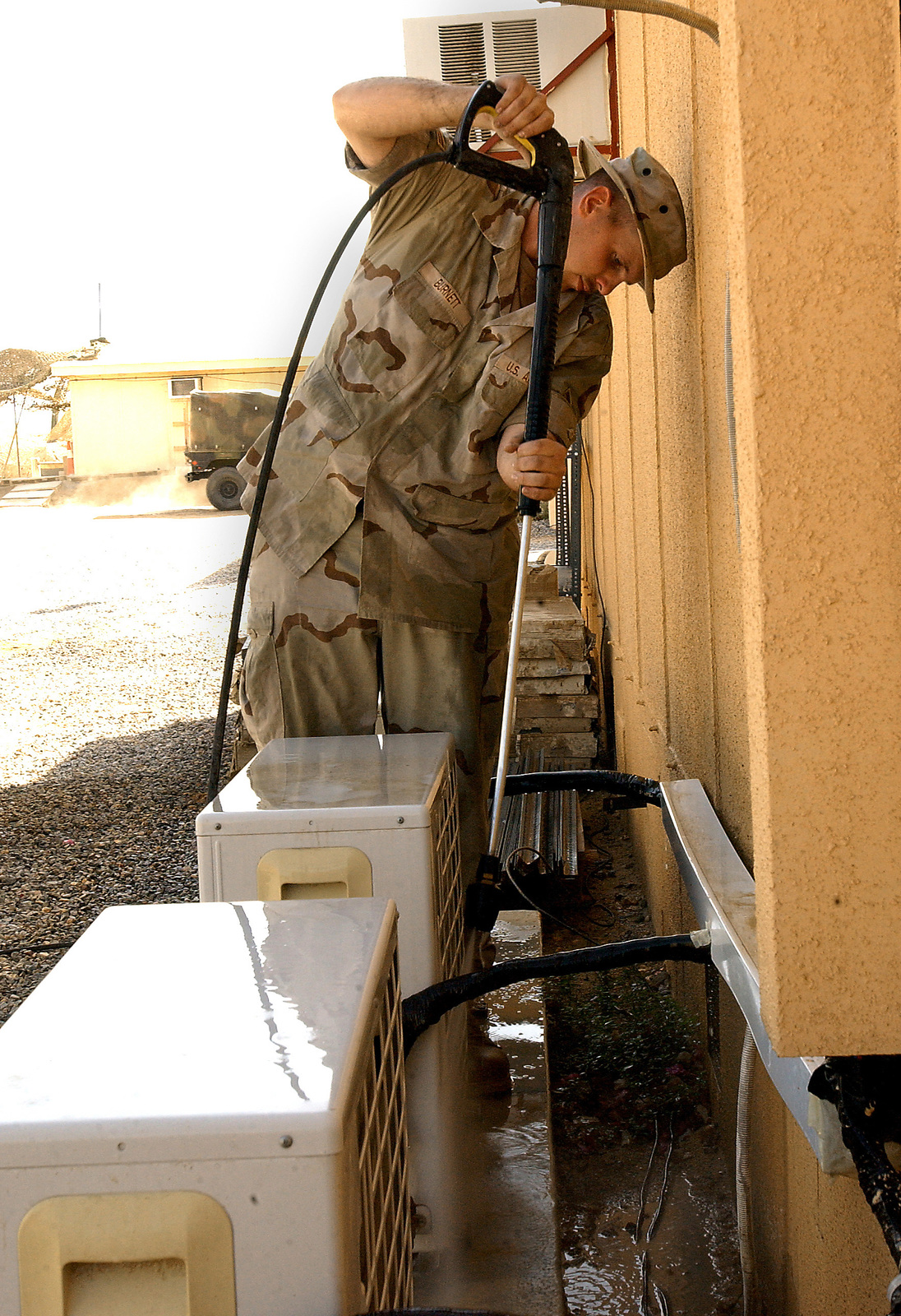 US Air Force (USAF) AIRMAN First Class (A1C) Steve Burnett, 320th Expeditionary Civil Engineering Squadron (ECES), uses a high-pressure washer to rinses off an air conditioning unit filter during a routine maintenance check, while deployed at an undisclosed location in South West Asia, during Operation ENDURING FREEDOM