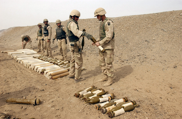 At a detonation pit, United States Navy and Army Explosive Ordnance Disposal (EOD) technicians prepare to destroy Chinese made 82mm Type 65 Recoilless Rifle and 82mm High Explosive Anti-Tank (HEAT) Recoilless Rifle Rounds, in support of Operation ENDURING FREEDOM