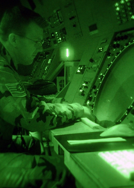 Viewed through a Night Vision lens, Technical Sergeant (TSGT) Robert Law, USAF, Air Traffic Controller, 48th Operations Support Squadron (OSS), 48th Fighter Wing (FW), Royal Air Force (RAF) Lakenheath, United Kingdom, monitors and works aircraft approach positions from the Radar Approach Control (RAPCON) center. The RAPCON monitors neighboring RAF Mildenhall aircraft and other civilian charters requiring radar service within a forty nautical mile radius of this base