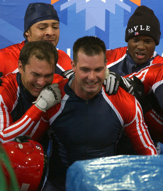 "As ""Switzerland-1"" nears the finish line, USA bobsled team members, Bill Schuffenhaur (back left), Brian Shimer (front left), World Class Athlete SPECIALIST Mike Kohn (center), and Army Reservist First Lieutenant Garrett Hines, USA, watch the monitor in anticipation of a medal. ""USA-1"" would win the sliver medal, while ""USA-2"" would win the bronze behind ""Germany-2"" at Utah Olympic Park in Park City, Utah during the 2002 WINTER OLYMPIC GAMES"