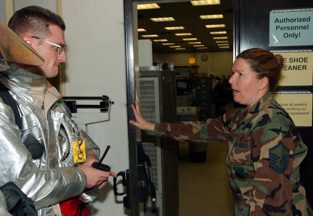 US Air Force (USAF) STAFF Sergeant (SSGT) Daniel Parker, with the 31st Civil Engineering Squadron (CES), responds to a smoke detector alarm with the help of MASTER Sergeant (MSGT) Laurie Newman, Test Measurement and Diagnostic Equipment Lab CHIEF