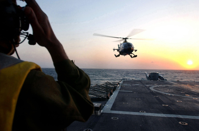 A US Navy (USN) Aircraft Handling Officer aboard the Guided Missile Cruiser USS YORKTOWN (CG 48) signals as an Mexican Navy MBB BO-105CB helicopter lands on deck during the 43rd annual UNITAS exercise. UNITAS is the largest multi-national naval exercise conducted with naval forces from the Caribbean Sea, South and Central America and the USN. The exercises focus on building multinational coalition while promoting hemispheric defense and mutual cooperation