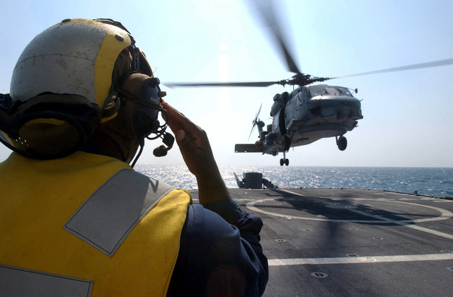 A US Navy (USN) Aircraft Handling Officer aboard the Guided Missile Cruiser USS YORKTOWN (CG 48) signals as an USN SH-60F Lamps III helicopter lands during the 43rd annual UNITAS exercise. UNITAS is the largest multi-national naval exercise conducted with naval forces from the Caribbean Sea, South and Central America and the USN. The exercises focus on building multinational coalition while promoting hemispheric defense and mutual cooperation