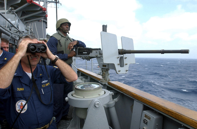 US Navy (USN) CHIEF Warrant Officer (CWO) Bill Dunn uses binoculars and stands watch while USN GUNNER's Mate 2nd Class (GM2) Remon Peterson mans the .50 caliber machine gun onboard the Guided Missile Cruiser USS Yorktown (CG 48) while participating in the 43rd annual UNITAS exercise. UNITAS is the largest multi-national naval exercise conducted with naval forces from the Caribbean Sea, South and Central America and the USN. The exercises focus on building multinational coalition while promoting hemispheric defense and mutual cooperation