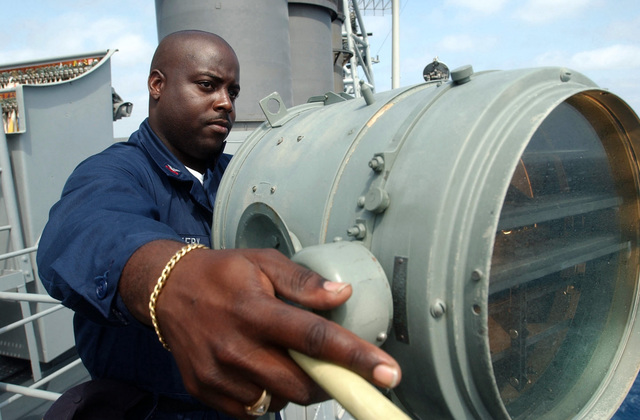 US Navy (USN) Signalman First Class (SM1) Roderick Dockery flashes signals aboard the US Coast Guard (USCG) FAMOUS CUTTER CLASS; Medium Endurance Cutter USCG THETIS (WMEC 910) during the 43rd annual UNITAS exercises. UNITAS is the largest multi-national naval exercise conducted with naval forces from the Caribbean Sea, South and Central America and the USN. The exercises focus on building multinational coalition while promoting hemispheric defense and mutual cooperation