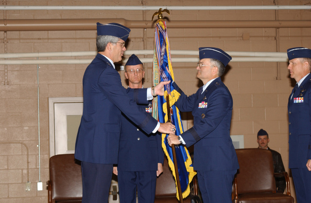 US Air Force (USAF) Major General (MGEN) John F. Regni (left), Commander, 2nd Air Force, passes the Unit Guidon to USAF Brigadier General (BGEN) Arthur J. Rooney, during the 82nd Training Wing (TRW) Change of Command Ceremony at Sheppard Air Force Base (AFB) Texas (TX). USAF BGEN Michael Collings Jr., Out-going Commander 82nd TRW is pictured far right and Command Sergeant Major (CSM) Robert W. Burleigh, stands center