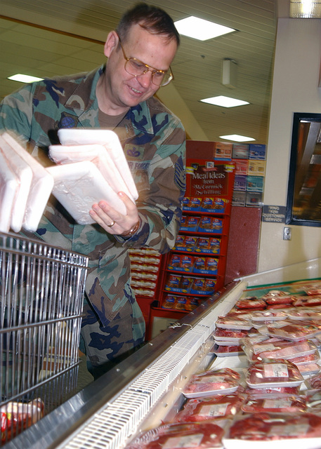 Technical Sergeant (TSGT) Michael Todd, USAF, 92nd Security Forces Squadron (SFS), 92nd Air Refueling Wing (ARW), Fairchild AFB, Washington grabs handfuls of meat products during a shopping spree at the base commissary as part of his award as Wing Non-Commissioned Officer (NCO) of the Year