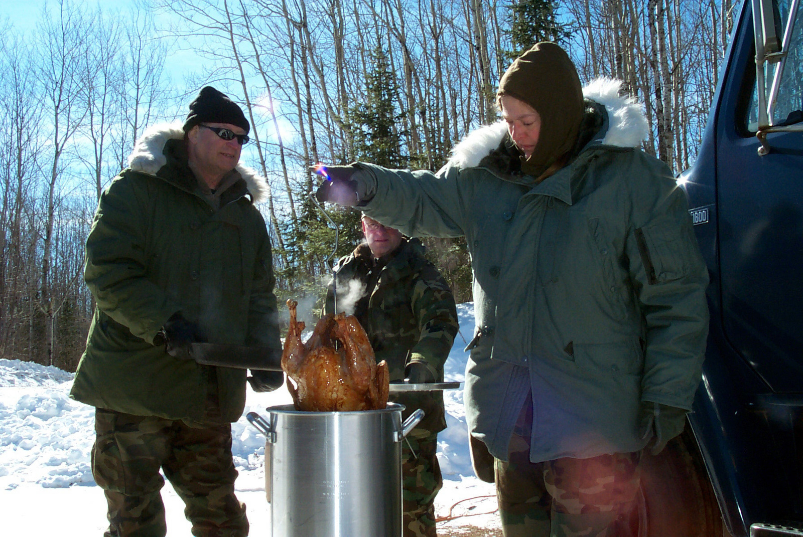 US Air Force (USAF) personnel assigned to the 148th Fighter Wing (FW), Minnesota Air National Guard (ANG), cook a deep fried turkey for lunch at the Pike Lake Crossing remote communication base. The Guardsmen are checkpoint volunteers for the annual 400-mile John Beargrease Sled Dog Marathon held along the north shore of Lake Superior, Minnesota (MN)