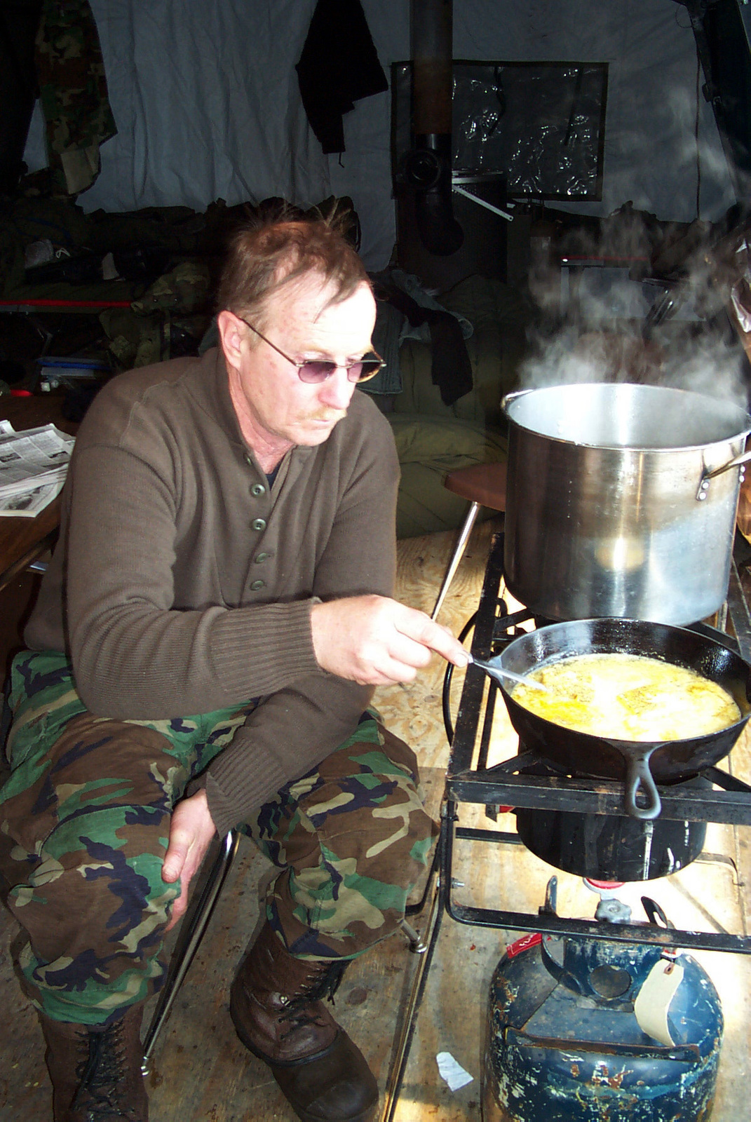 US Air Force (USAF) Technical Sergeant (TSGT) Everett Erickson, 148th Fighter Wing (FW), Minnesota Air National Guard (ANG), uses a field stove to prepare breakfast at the Pike Lake Crossing remote communication base. TSGT Erickson is one of the checkpoint volunteers, from the Minnesota ANG, for the annual 400-mile John Beargrease Sled Dog Marathon held along the north shore of Lake Superior, Minnesota (MN)