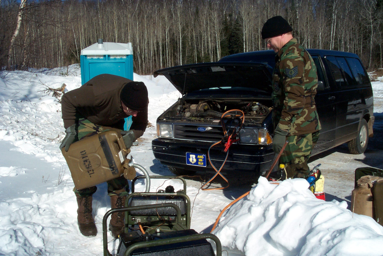 US Air Force (USAF) Technical Sergeant (TSGT) Everett Erickson (left) and USAF TSGT Rawn Nilsen, 148th Fighter Wing, Minnesota Air National Guard (ANG), refuel a portable generator at Pike Lake Crossing. The Guardsmen are checkpoint volunteers for the annual 400-mile John Beargrease Sled Dog Marathon held along the North Shore of Lake Superior, Minnesota (MN)