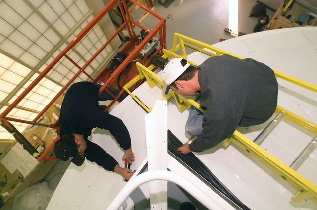 Robert Blankenship (left), and Todd Crooks (right), flight simulator mechanics from Binghamton Simulator Company make fitting adjustments to sheet metal trim during the installation of the Visual Upgrade Enhancement mirror assembly for the KC-135 Stratotanker flight trainer at the KC-135 flight training facility at MacDill AFB, Florida. The mirror is a part of planned upgrades to the facility to include software upgrades and the installation of the Six Degrees of Freedom (DOF) motion system due in October 2002. When completed, The upgrades will provide a more realistic training environment for the flight crews