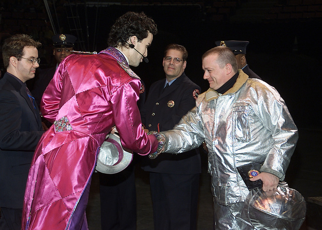 STAFF Sergeant (SSGT) Dominick Roselli, USAF, 514th Civil Engineer Squadron (CES), 514th Air Mobility Wing (AMW), McGuire AFB, New Jersey (NJ), is greeted by Ringmaster Kevin Vernardos, Ringling Brothers and Barnum & Bailey Circus, during a ceremony held March 6, 2002, at the Continental Arena in Newark, NJ. The Ringling Brothers Circus presented a plaque to SSGT Roselli in recognition of his efforts at Ground Zero and service to the nation. SSGT Roselli's civilian job is as a firefighter for the Lakehurst Naval Air Station. One of four Lakehurst firefighters on the NJ urban search and rescue team, SSGT Roselli responded to the World Trade Center (WTC) attack and worked for a week and a...