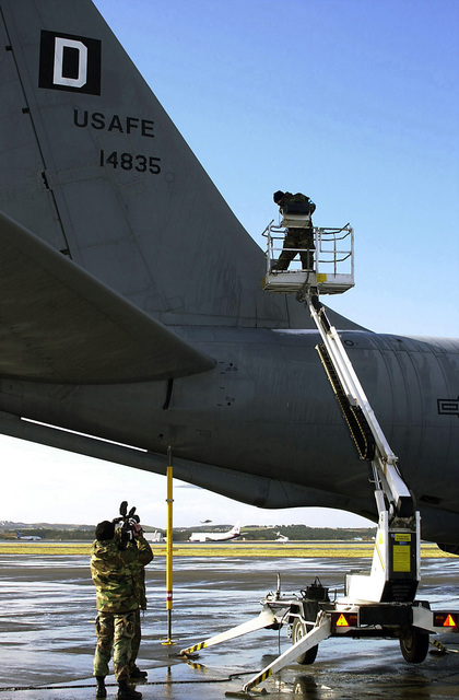 A US Air Force (USAF) Combat Camera Videographer documents USAF STAFF Sergeant (SSGT) Dan Hanson, 100th Maintenance Squadron, as he positions a hydraulic aircraft lift, before inspecting a Q-Inlet valve on the tail section of a USAF KC-135R Stratotanker aircraft, at Sola Air Station, Norway during Exercise STRONG RESOLVE 2002