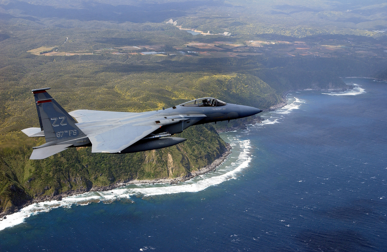 A US Air Force (USAF) F-15C Eagle aircraft piloted by USAF Captain (CPT) Michael Love, 67th Fighter Squadron (FS), 18th Fighter Wing (FW), Kadena Air Base, Japan, flies during a training mission over the Southern coast of Okinawa, Japan