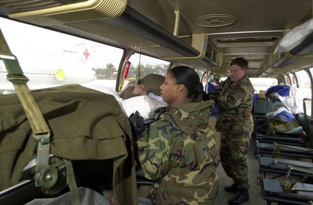 US Air Force (USAF) STAFF Sergeant (SSGT) Christine Hill (foreground) and USAF Major (MAJ) William Osborne, 86th Aeromedical Evacuation Squadron (AES), position an injured service member inside medical transport vehicle at Ramstein Air Base, Germany. The service members are being transported to Landstuhl Regional Medical Center for treatment