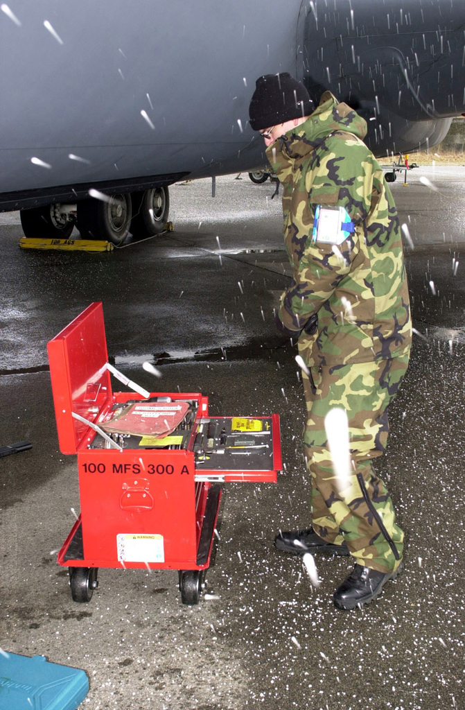 US Air Force (USAF) STAFF Sergeant (SSGT) Dan Hanson, 100th Maintenance Squadron takes an inventory of his tools during a sudden hailstorm at Sola Air Station, Norway during Exercise STRONG RESOLVE 2002