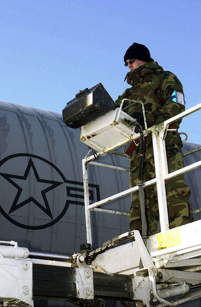 US Air Force (USAF) STAFF Sergeant (SSGT) Dan Hanson, 100th Maintenance Squadron, uses a hydraulic aircraft lift to inspect a Q-Inlet valve on the tail section of a USAF KC-135R Stratotanker aircraft at Sola Air Station, Norway during Exercise STRONG RESOLVE 2002