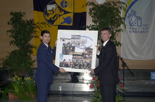 "At a reception after the Grand Tattoo Ceremony at Ramstein Air Base, Germany, Mr. Klaus Layes (right), Ramstein-Miesenbach Mayor presents a montage of""50 years of Friendship and Freedom""as gift to Brigadier General (BGEN) Mark A. Volcheff, Commander, 86th Airlift Wing (AW). The presentation of the German Tattoo Ceremony is one of the highest honors in the German military"