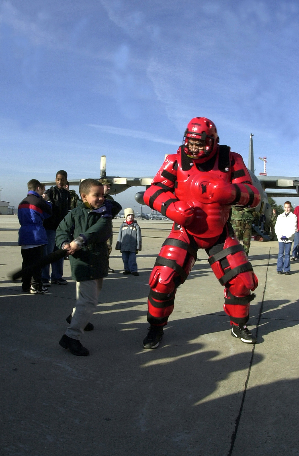 US Air Force (USAF) STAFF Sergeant (SSGT) Duke McDuffie, 786th Security Forces Squadron (SFS), wears a Redman Training Suit, as 6-year old Isaac Johnson takes a good swing at him, during the annual Shadow Day event, at Ramstein Air Base, Germany