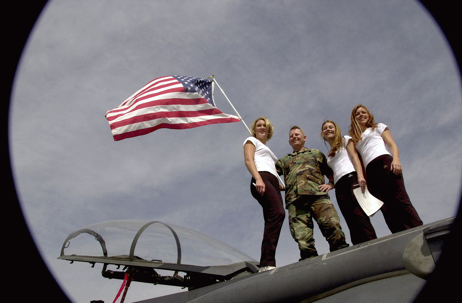 Low angle, fisheye lens view showing US Air Force (USAF) MASTER Sergeant (MSGT) Thomas Carter, First Sergeant for the 494th Fighter Squadron (FS), deployed at Incirlik Air Base (AB), Turkey, posing for a photograph with three members of the National Football League (NFL), Tampa Bay Buccaneers, Cheerleading Squad, while standing atop a USAF F-15E Strike Eagle aircraft. Members of the squad are visiting with deployed military personnel in support of Operation ENDURING FREEDOM