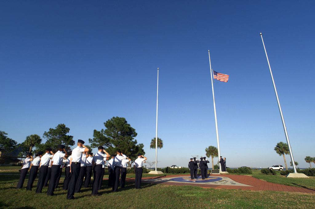 Twenty United States Air Force (USAF) members from the 6th Air Mobility Wing (AMW) render salute as the honor guard lowers the US flag during a retreat ceremony held at the MacDill Air Force Base (AFB) Memorial Park
