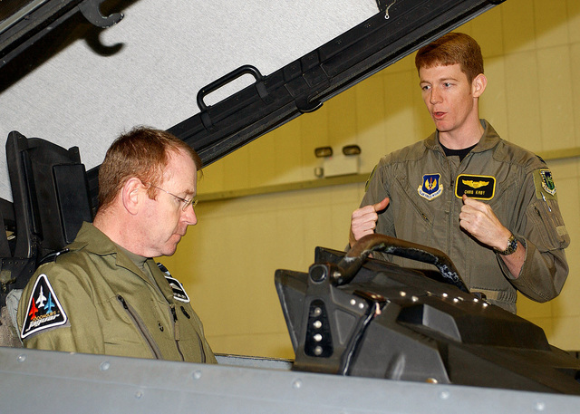 Captain (CAPT) Chris Kirby (right), USAF, Pilot, 493rd Fighter Squadron (FS), 48th Fighter Wing (FW), Royal Air Force Lakenheath, United Kingdom, demonstrates ejection procedures to Air Vice-Marshal Philip Sturley, Assistant CHIEF of the Air STAFF, Ministry of Defense, at the Operation Support Squadron's (OSS) F-15E Strike Eagle flight simulator. Air Vice-Marshal Sturley was invited up from London by Major General (MGEN) Kenneth Hess, USAF, Commander, 3rd Air Force, to visit RAF Mildenhall and to receive an orientation flight in the F-15E Strike Eagle