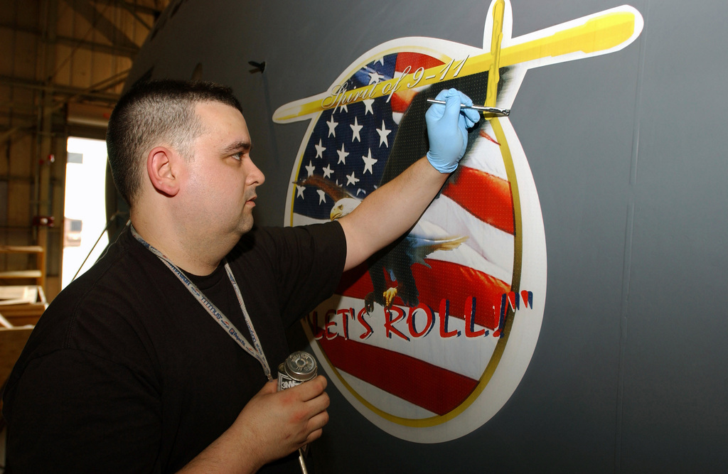 "A member of the 436th Equipment Maintenance Squadron (EMS) seals the ""Spirit of 9-11"" decal on a C-5 Galaxy at Dover Air Force Base, Delaware, on 18 March 2002. The plane will be officially named in an upcoming naming ceremony. ""Lets Roll,"" the now famous phrase United Airlines Flight 93 passenger Todd Beamer uttered as he and fellow passengers foiled terrorist hijackers, bringing down the aircraft in a Pennsylvania field that fatal morning"