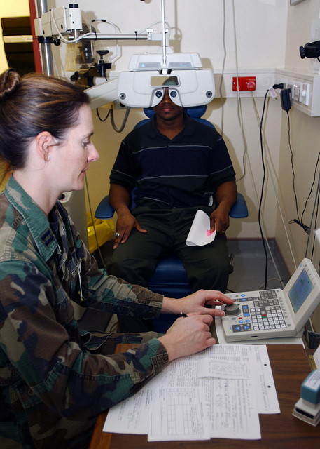 Captain (CAPT) Michelle Koe (left), USAF, Optometrist, 48th Aerospace Medicine Squadron (AMDS), 48th Fighter Wing (FW), Royal Air Force Lakenheath, United Kingdom, performs a refractor test with a NIDEK Refraction System RT-2100 to determine a prescription for AIRMAN First Class (A1C) Charles Everett, USAF, 48th Equipment Maintenance Squadron (EMS), Sheet Metal shop. The 48th AMDS Optometry Clinic see over 100 patients a day and is the only Department of Defense (DoD) eye clinic in the United Kingdom, with 99.9% of all cases that come into the clinic can be handled in-house with no referrals for further treatment