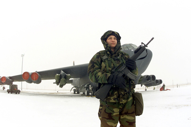 US Air Force (USAF) AIRMAN (AMN) Alicia Bates, 23rd Bomb Wing (BW) Security Forces Squadron (SFS), armed with a 5.56mm M16A2 rifle, stands guard duty near a B-52H Stratofortress aircraft on the snow covered flight line at Minot Air Force Base (AFB), North Dakota (ND), during the alert status part of Exercise PRAIRIE VIGILANCE 2002