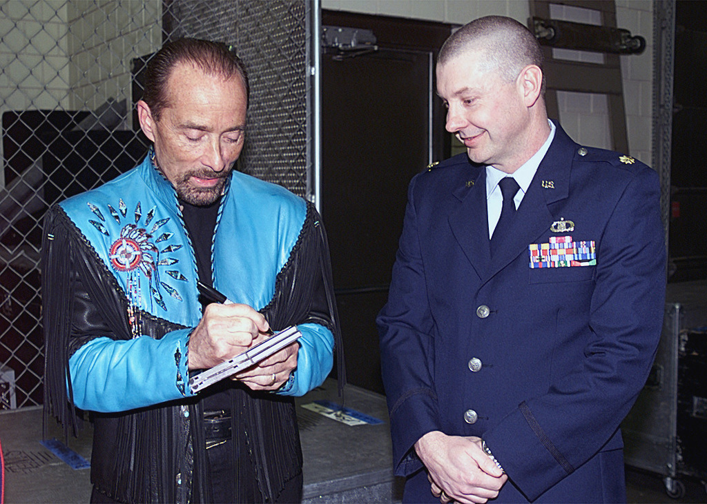 Music star, Lee Greenwood (left), signs an autograph for Major (MAJ) Randy Bass, USAF, 28th Operations Support Squadron (OSS), Weather Flight Commander, Ellsworth Air Force Base, South Dakota, prior to his March 21st performance at the Rushmore Plaza Civic Center. MAJ Bass, and his family were invited to meet Mr. Greenwood prior to the show