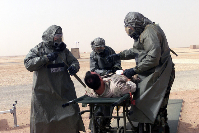 """The decontamination team from the 56th Medical Group (MDG), Luke Air Force Base, Arizona, strap a patient to a gurney for transportation to the decontamination tent at Prince Sultan Air Base, Kingdom of Saudi Arabia. At the tent, they will clean him of all chemical agents. The team members call themselves """"The Dirty Dozen"""" and are here in support of Operation SOUTHERN WATCH. They are outfitted in Mission-Oriented Protective Posture response level 4 (MOPP-4) with a Toxicological Agent Protective (TAP) Apron as an over garment"""