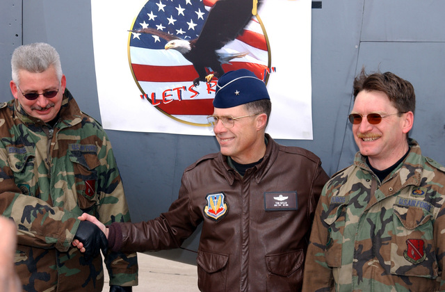 """US Air Force (USAF) Brigadier General (BGEN) Thomas G. Cutler (center), Commander, 127th Wing, poses for a photograph with two Air National Guard (ANG) Crew Chiefs, MASTER Sergeant (MSGT) Mike Edwards (left) and Technical Sergeant (TSGT) Mark Dubois, in from of the new """"Lets Roll"""" logo that will be displayed on one of the 127th Wings C-130 Hercules aircraft, on the flight line at Selfridge Air National Guard Base (ANGB) Michigan (MI)"""