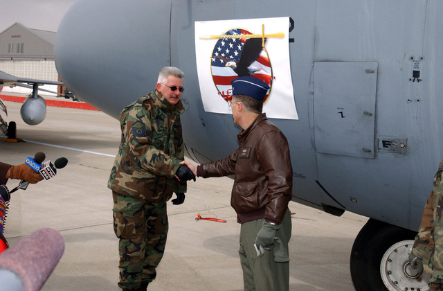"""US Air Force (USAF) Brigadier General (BGEN) Thomas G. Cutler (right), Commander, 127th Wing, shakes hands with Air National Guard (ANG) Crew Chiefs, MASTER Sergeant (MSGT) Mike Edwards in from of the new """"Lets Roll"""" logo that is displayed on one of the 127th Wings C-130 Hercules aircraft, on the flight line at Selfridge Air National Guard Base (ANGB) Michigan (MI)"""