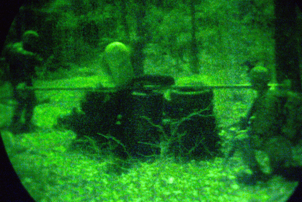 """Seen through a night vision scope, Marines from Battalion Landing Team (BLT) 2nd Battalion, 2nd Marines (2/2), Fox Company, surround and secure an """"enemy"""" position at Quantico, Virginia, during a Helicopter borne raid conducted as part of the 24th Marine Expeditionary Units (MEU) pre-deployment training at Fort A. P. Hill, Virginia"""