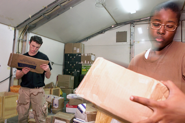 SENIOR AIRMAN (SRA) Jason Privett (left), USAF, and AIRMAN First Class (A1C) Denesha Hendrix, USAF, Postal Clerks assigned to the Camp Justice Postal Center, read the names on packages as they prepare them for sorting