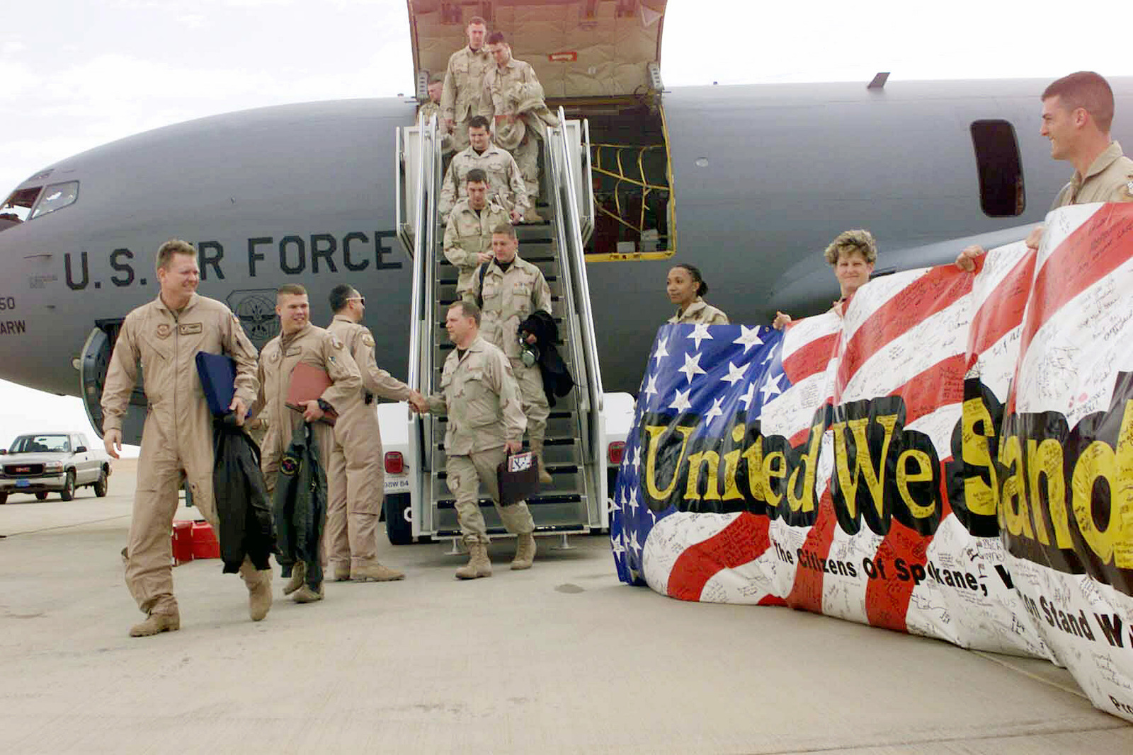 """As they come off the KC-135 Stratotanker, members from the 92nd and 97th Air Refueling Squadrons (ARS), Fairchild Air Force Base, Washington, are welcomed to Prince Sultan Air Base, Kingdom of Saudi Arabia, by members of the 363rd Expeditionary Air Refueling Squadron (EARS). Residents of Spokane, WA, signed the """"United We Stand"""" banner"""