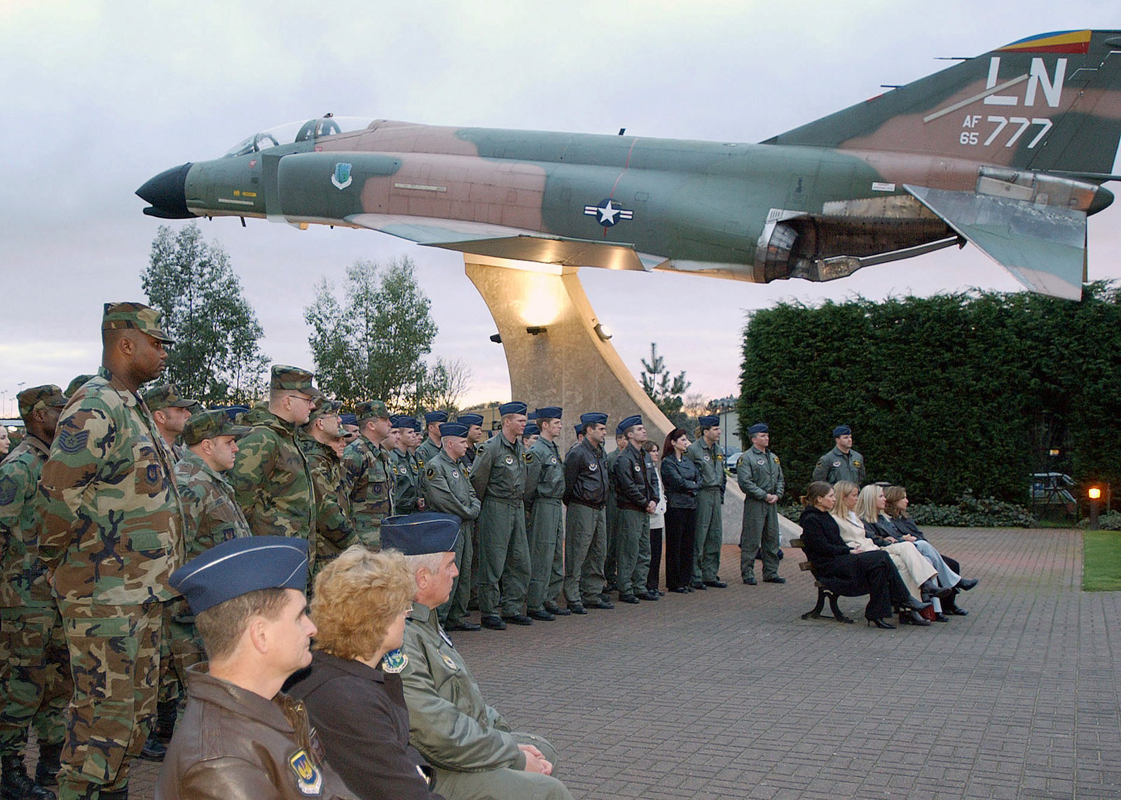 """Under the F-4C Phantom II static display, members of the 493rd Fighter Squadron (FS), and 48th Operations Group (OG), 48th Fighter Wing (FW), Royal Air Force Lakenheath, United Kingdom, listen to the chaplain during the ceremony held at the Wings of Liberty Park. The ceremony is held to honor and remember Lieutenant Colonel (LCOL) Kenneth """"Buster"""" Hyvonen and Captain (CAPT) Kirk """"Jammer"""" Jones, whose F-15Cs crashed in the Scottish Highlands a year ago"""