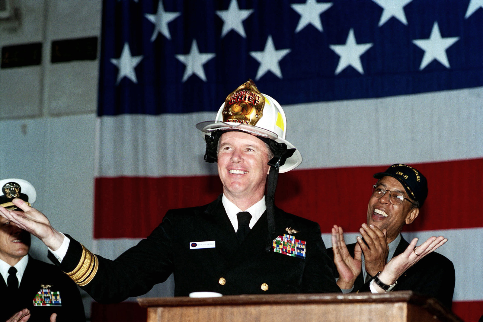 US Navy (USN) Rear Admiral (RADM) Mark Fitzgerald, Commander, Carrier Group Eight (CCG 8) (CVN 71) dons a honorary Fire Chiefs Helmet, presented by members of the New York City Fire Department during a return to the World Trade Center Flag Ceremony, held aboard the Aircraft Carrier USS THEODORE ROOSEVELT (CVN 71)