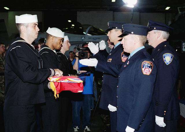 """US Navy (USN) Sailors and members of the New York City Police Department and New York City Fire Department take part in a formal ceremony held aboard the Aircraft Carrier USS THEODORE ROOSEVELT (CVN 71) to return flag flown above the World Trade Centers back to the City of New York. The Flags were the first to be raised above """"ground zero"""" at the site of the attack on the New Yorks World Trade Centers and were flown aboard CVN 71 during combat missions in support of Operation ENDURING FREEDOM"""