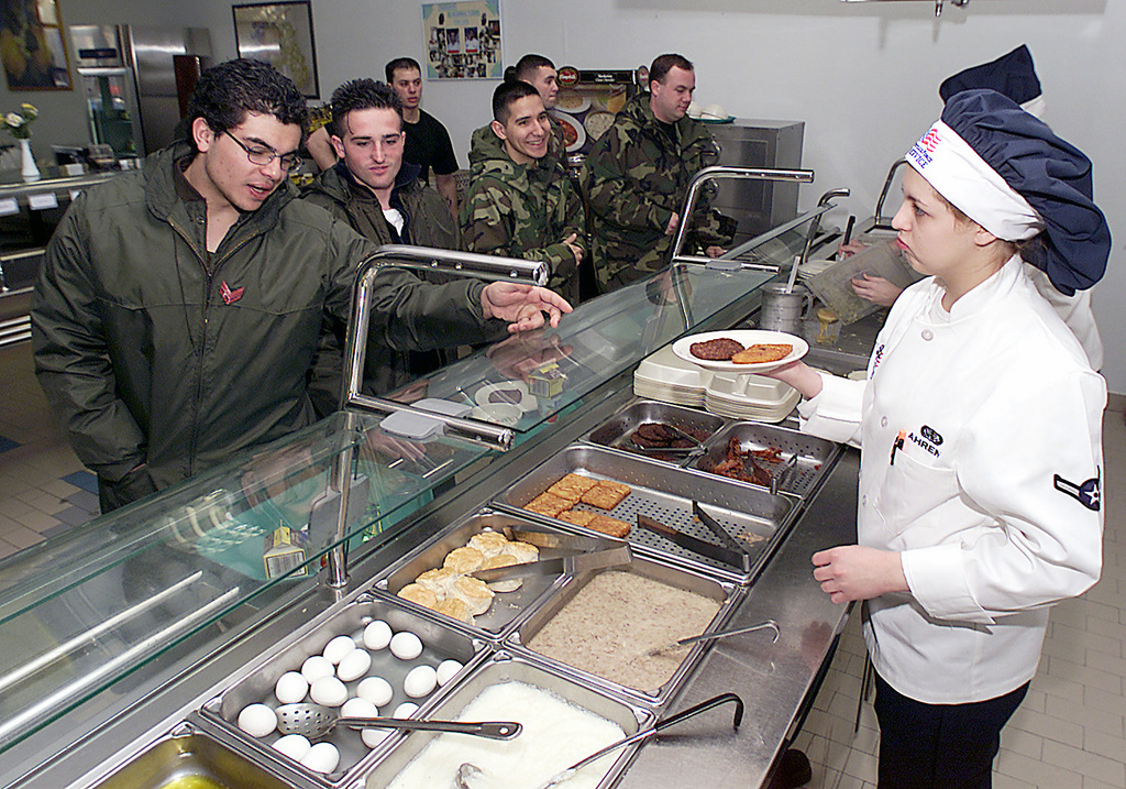 All in a days work as AIRMAN (AMN) Elizabeth Ahrens, USAF, 31st Services Squadron (SVS), serves up some breakfast for the Italian Army at the Dolimetti Dining Facility at Aviano Air Base, Italy