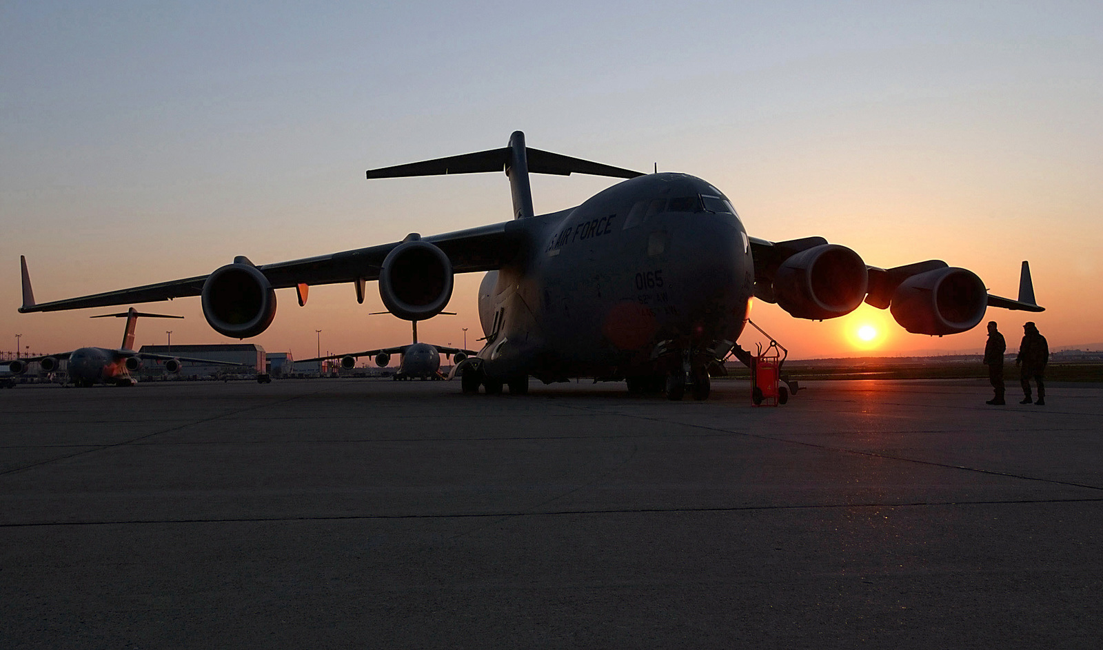 On the flightline at Rhein-Main Air Base, Germany, two US Air Force maintenance members stand beside a C-17A Globemaster III at sunset during Operation ENDURING FREEDOM