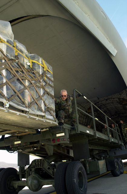 SENIOR MASTER Sergeant (SMSGT) Charles Rehnert, USAF, 271st Combat Communications Squadron (CBCS) helps pull another pallet of equipment onto a C-17A Globemaster III, 437th Airlift Wing (AW), Charleston AFB, South Carolina. The C-17 arrived to take equipment and personnel from the 271st Combat Communications Squadron (CCS) to an undisclosed location in support of Operation ENDURING FREEDOM