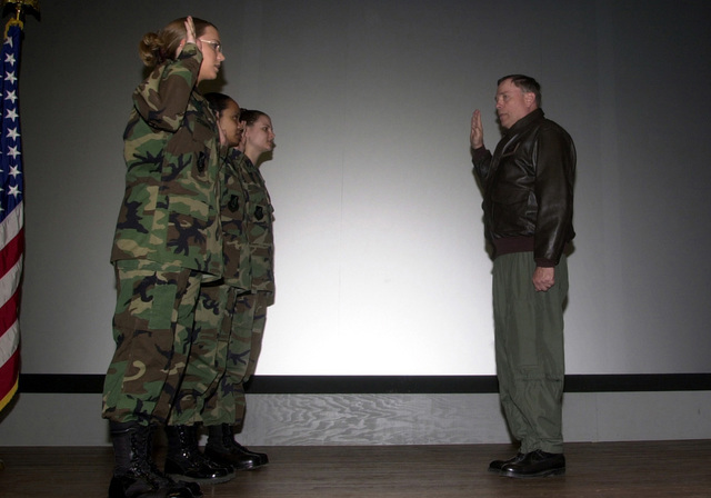 United States Air Force (USAF) CHIEF of STAFF (CS) of the Air Force, General (GEN) John P. Jumper re-enlists three airman of the 8th Fighter Wing (FW) on a visit to Kunsan Air Base, Republic of Korea (KOR), Saturday, March 30, 2002