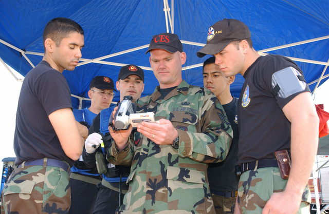 US Air Force (USAF) STAFF Sergeant (SSGT) Gregg Wozniak, from 366th Civil Engineer Squadron (CES), Explosive Ordnance Disposal (EOD) Flight, Mountain Home Air Force Base (AFB), Idaho (ID), shows video footage captured earlier of the suspicious package to members of the survey team. Watching are, AIRMAN First Class (A1C) John Lopez and A1C Felix Jauregui, AIRMAN (AMN) Kyle Leger, from the Bio-Environmental Flight, 366th Aeromedical Dental Squadron (ADS), Mountain Home Air Force Base (AFB), US Army (USA) STAFF Sergeant (SSG) Donnie Johnson and USA SSG Jeremy Hamrick, from the 101st Weapons of Mass Destruction (WMD), Civil Support Team (CST). This was a local Major Accident Response...