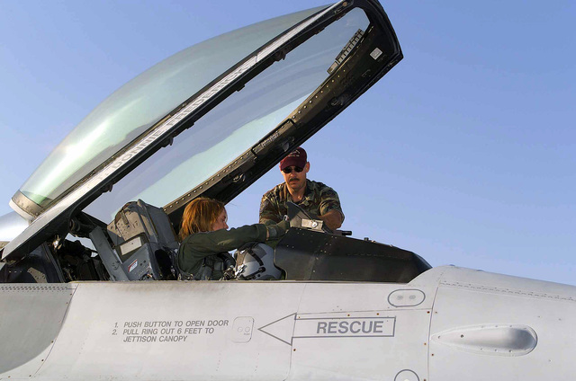 Technical Sergeant (TSGT) Kevin J. Jones, USAF, Crewchief, assists Second Lieutenant (2LT) Kristin L Bass, USAF, as she prepares to egress her F-16C Fighting Falcon after her first unit training flight. Both are with the 188th Fighter Wing, Arkansas Air National Guard, Fort Smith, Arkansas