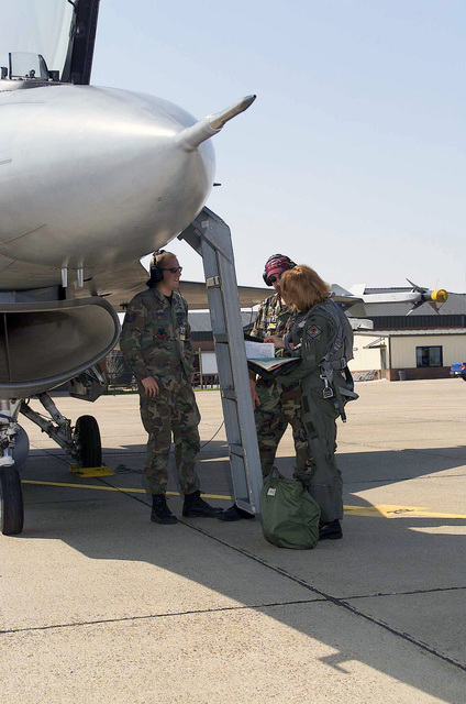 The first female F-16 Fighting Falcon Pilot, Second Lieutenant (2LT) Kristin L Bass, USAF, checks the maintenance logs with crewchiefs Technical Sergeant (TSGT) Robert M Grimm, USAF, and TSGT Kevin J. Jones, USAF, prior to her first training mission flight with the 188th Fighter Wing, Arkansas Air National Guard, Fort Smith, Arkansas