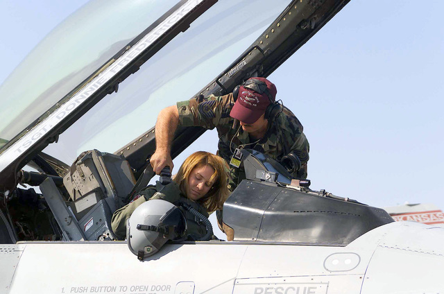 The first female F-16 Fighting Falcon Pilot, Second Lieutenant (2LT) Kristin L Bass, USAF, gets strapped into her F-16C Fighting Falcon by crewchief Technical Sergeant (TSGT) Kevin J. Jones