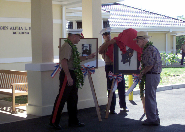 During the Dedication Ceremony for the newly renovated LEGEN Alpha L. Bowser building at Kaneohe, Hawaii General Bowser presents Brigadier General (BGEN) Jerry C. McAbee, USMC, Commanding General Marine Corps Base Hawaii (MCBH) with a portrait of himself, painted by his daughter. The portrait will hang in the lobby of the newly renovated Temporary Lodging Facility